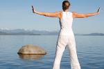Women meditating by a lake